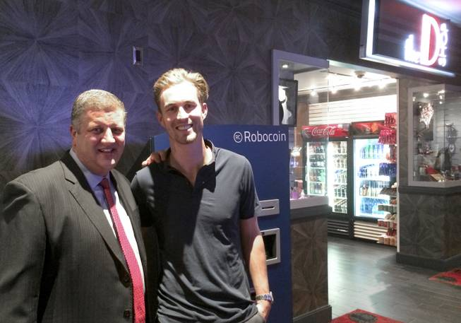 CEO of the D Derek Stevens, left, and Robocoin CEO Jordan Kelley stand next to a Bitcoin ATM, the first available at a casino property.