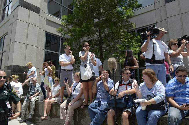 In this July 5, 2011 file photo, spectators wait outside the Orange County Courthouse to hear the announcement of the verdict in the Casey Anthony trial in Orlando, Fla. Media coverage of the Casey Anthony trial at the Orange County Courthouse in Orlando and the George Zimmerman trial in the nearby Seminole County Courthouse in Sanford has turned the local legal community into semi-celebrities.