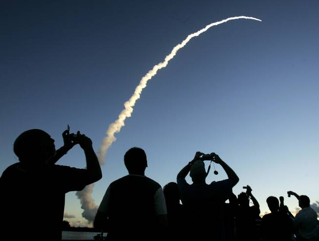 In this  Sept. 27, 2007 file photo, spectators at Jetty Park pier watch as a Delta II rocket lifts off from the Cape Canaveral Air Force Station in Cape Canaveral, Fla.