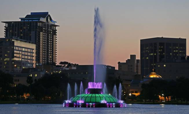 In this May 19, 2014, photo, water rises from a five-decade-old, green, multi-tiered fountain on Lake Eola that is the official icon of the city as the sun sets in Orlando, Fla. Every night, passersby are treated to a six-minute water show from the fountain featuring multicolored bursts of water timed to music.