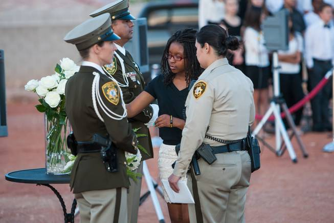 As the names of fallen officers are read, the family of fallen LVMPD Officer James L. Manor adds a white rose in his memory to the memorial bouquet during the Southern Nevada Law Enforcement Memorial ceremony at Police Memorial Park in Las Vegas Thursday, May 22, 2014.