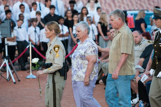 As the names of fallen officers are read, the parents of fallen LVMPD Officer Milburn Beitel approaches the memorial bouquet to pay honor in his memory during the Southern Nevada Law Enforcement Memorial ceremony at Police Memorial Park in Las Vegas Thursday, May 22, 2014.