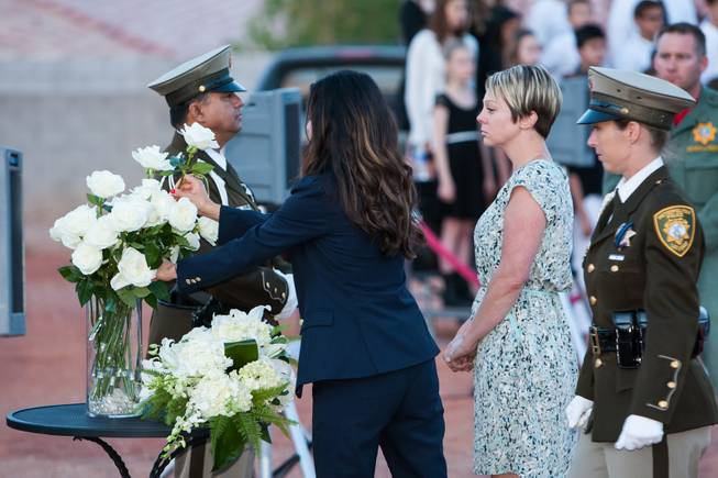 As the names of fallen officers are read, the family of fallen LVMPD Officer David VanBuskirk adds a white rose in his memory to the memorial bouquet during the Southern Nevada Law Enforcement Memorial ceremony at Police Memorial Park in Las Vegas Thursday, May 22, 2014.