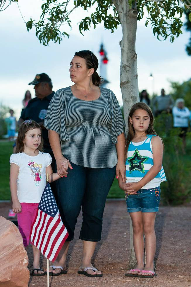 Kelli McCrimmon and her daughters, Joslynne, 4, and Jadynne, 8, listen with reverence as the names of fallen officers are read during the Southern Nevada Law Enforcement Memorial ceremony at Police Memorial Park in Las Vegas Thursday, May 22, 2014.