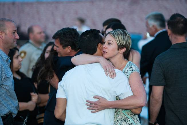 Family members of fallen officer LVMPD Search and Rescue Officer David VanBuskirk are embraced by other attendees during the Southern Nevada Law Enforcement Memorial ceremony at Police Memorial Park in Las Vegas Thursday, May 22, 2014.