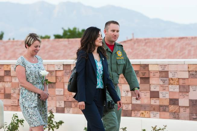Family members of fallen officer LVMPD Search and Rescue Officer David VanBuskirk and Search and Rescue Officer Connell walk past the memorial wall where VanBuskirk's name will be added during the Southern Nevada Law Enforcement Memorial ceremony at Police Memorial Park in Las Vegas Thursday, May 22, 2014.