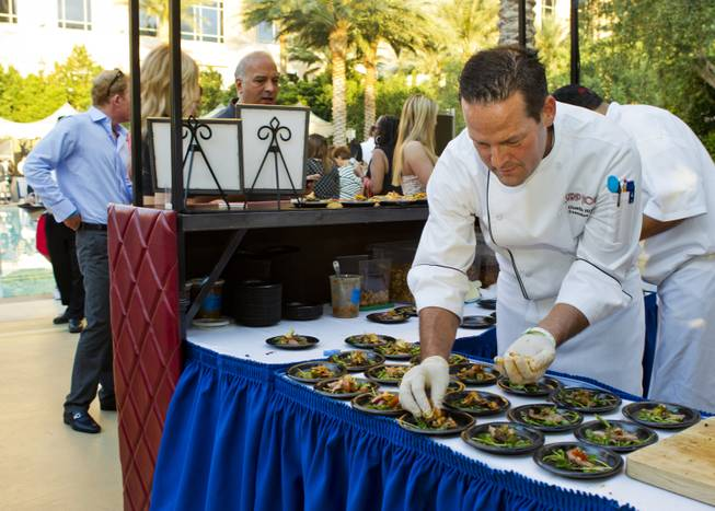 Strip House executive chef Dustin Rixey prepares a dish to serve during the Epicurean Affair presented by the Nevada Restaurant Association at the Palazzo on Thursday, May 22, 2014.
