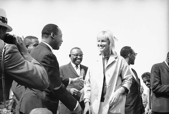 Integration leader Martin Luther King, left, greets actress May Britt one of several Hollywood stars present as she and her husband Sammy Davis arrived at the platform at a mass civil rights rally at Wrigley Field in Los Angeles, May 26, 1963. Dr. King was joined by several other leaders of the Birmingham integration movement.