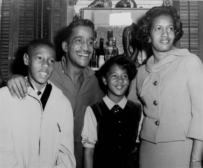 "Entertainer and civil rights activist Sammy Davis, Mrs. Medgar Evers, widow of slain activist Medgar Evers, and her children Darrell and Reene, are all smiles in Sammy's dressing room backstage after Saturday's matinee of the musical ""Golden Boy"" at the Majestic Theatre, NYC, January 5, 1965."