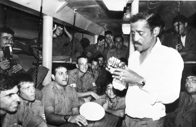 Entertainer Sammy Davis Jr is inspecting an ashtray made out of bullet cartridges which was given to him by Israeli missile boat crew which he visited in Northern Israel, July 14, 1982.