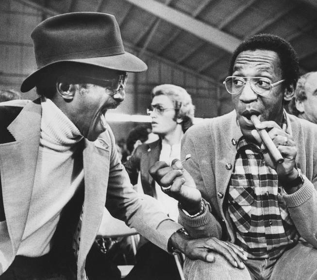 Entertainer Sammy Davis Jr. shares a laugh with comedian Bill Cosby right, as he lights his cigar while attending the light heavyweight fight in Las Vegas Saturday , February 27, 1979 . The scheduled fight between Mike Rossman and Victor Galindez was indefinitly postponed.
