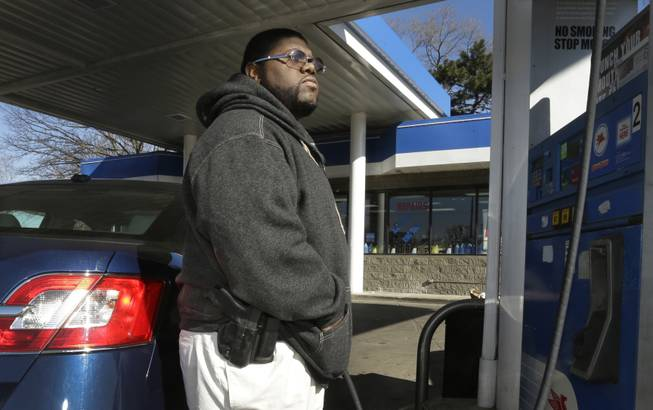 In a photo from April 9, 2014, Greg Champion wears a gun while pumping gas in Detroit. To avoid becoming a carjacking victim, Champion wears a handgun on his hip whenever he's pumping gas. Through May 19, Detroit has recorded 191 carjackings in 2014.
