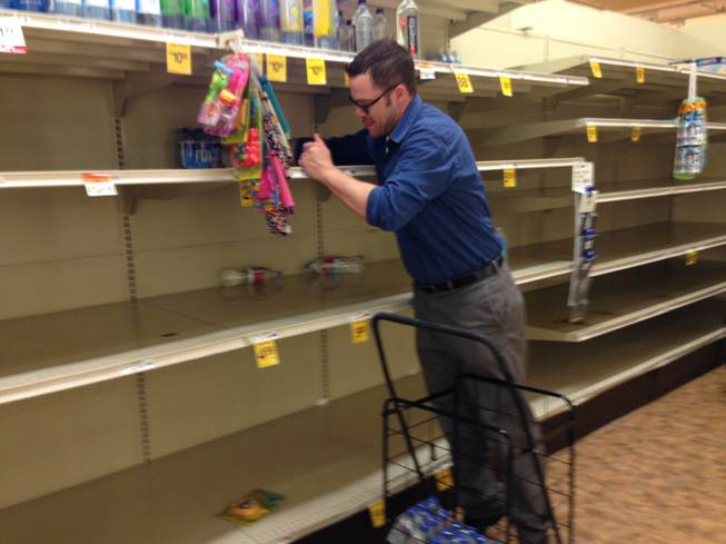 Matt Smith purchases some of the last bottled water available Friday, May 23, 2014, at a Safeway store in Portland, Ore. A citywide boil notice was issued Friday for Portland, after E. coli was detected in the water supply, causing a rush on bottled water.