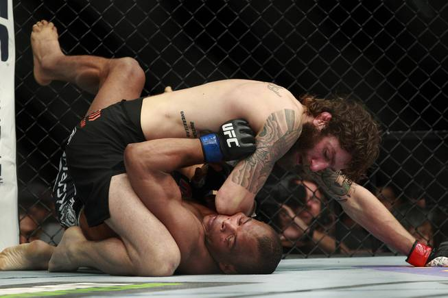 Lightweight Michael Chiesa drops an elbow onto the face of Francisco Trinaldo during their fight at UFC 173 Saturday, May 24, 2014 at the MGM Grand Garden Arena. Chiesa won a unanimous decision.