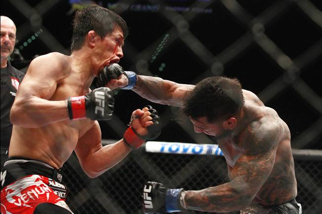 Takeya Mizugaki is hit with a right from Francisco Rivera during their fight at UFC 173 Saturday, May 24, 2014 at the MGM Grand Garden Arena. Mizugaki won by unanimous decision.