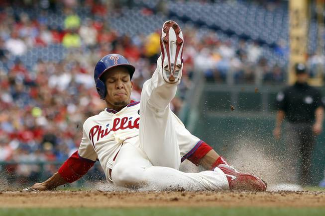 Philadelphia Phillies' Cesar Hernandez slides into home plate to score on a single by Ben Revere during the second inning of a baseball game against the Los Angeles Dodgers, Saturday, May 24, 2014, in Philadelphia.