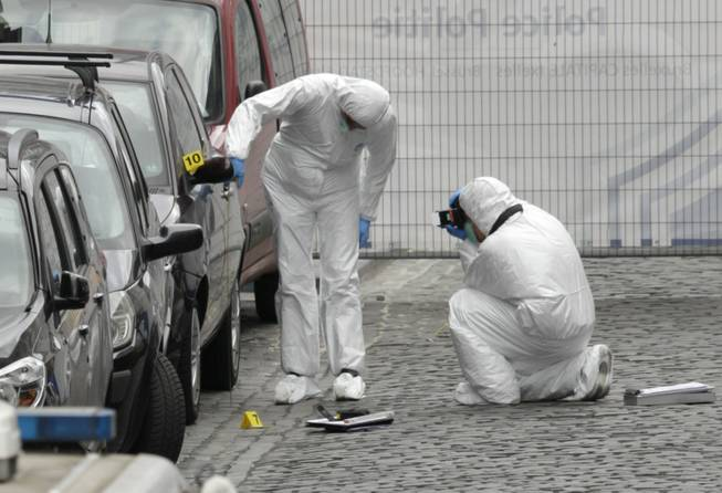 Forensic experts examine the site of a shooting at the Jewish museum in Brussels on Saturday, May 24, 2014. Belgian officials say that at least three people have been killed in gunfire at the Jewish Museum in Brussels.