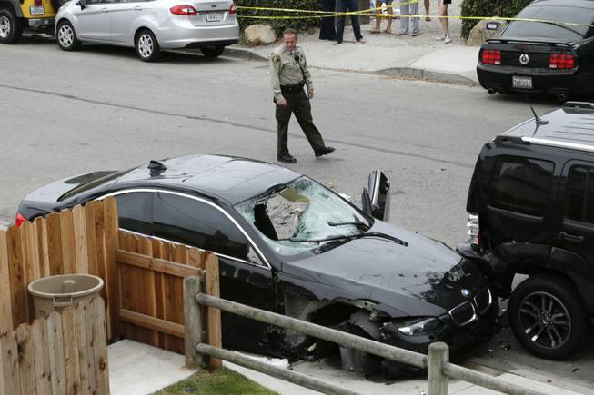 A Santa Barbara County deputy sheriff looks at the black BMW sedan driven by a drive-by shooter on Saturday, May 24, 2014, in Isla Vista, Calif. The shooter went on a rampage near a Santa Barbara university campus that left seven people dead, including the attacker, and others wounded, authorities said Saturday.