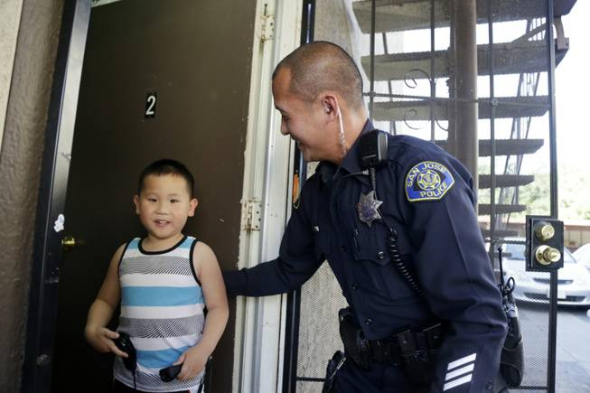 In this May 21, 2014 photo, San Jose police officer Huan Nguyen, right, visits with Steven Lam in San Jose, Calif. Nguyen came to the aid Lam and his family after the boy's father, Phuoc Lam, was killed during a road rage incident. Just two weeks since the murder, close to $100,000 in aid has poured in, from the local Vietnamese community and far beyond, including Houston, Boston, New York, even London.
