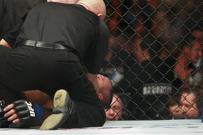 Dan Henderson is attended to after being choked out by Daniel Cormier during their fight at UFC 173 Saturday, May 24, 2014 at the MGM Grand Garden Arena. Cormier won with a rear naked choke in the third round.