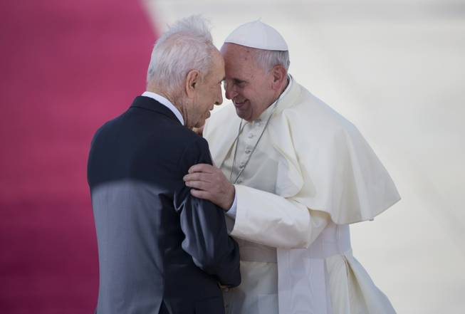 Pope Francis, right, talks with Israeli President Shimon Peres, during an official arrival ceremony at Ben Gurion airport near Tel Aviv, Israel, on Sunday, May 25, 2014. Pope Francis took a dramatic plunge Sunday into Mideast politics while on his Holy Land pilgrimage, receiving an acceptance from the Israeli and Palestinian presidents to visit him at the Vatican next month to discuss embattled peace efforts. The summit was an important moral victory for the pope, who is named after the peace-loving Francis of Assisi. Israeli-Palestinian peace talks broke down in late April, and there have been no public high-level meetings for a year.