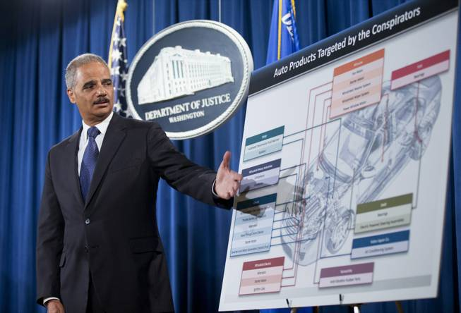 This Sept. 26, 2013 file photo shows Attorney General Eric Holder pointing to an illustrations of the auto parts during a news conference at the Justice Department in Washington. A federal investigation into price fixing in the auto parts industry, made public four years ago with FBI raids in the Detroit area, has mushroomed into the largest antitrust investigation in Justice Department history — and authorities say it's not over yet.