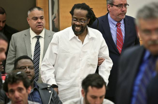In this May 6, 2014 file photo, Robert Hill, center, smiles as he is escorted into Brooklyn Supreme Court in New York. Hill and his half-brothers Alvena Jennette and Darryl Austin were exonerated in a decades-old conviction investigated by retired homicide detective Louis Scarcella, who has had some of his tactics have come into question. The Brooklyn District Attorney's Conviction Review Unit is currently re-examining more than cases that Scarcella worked on.