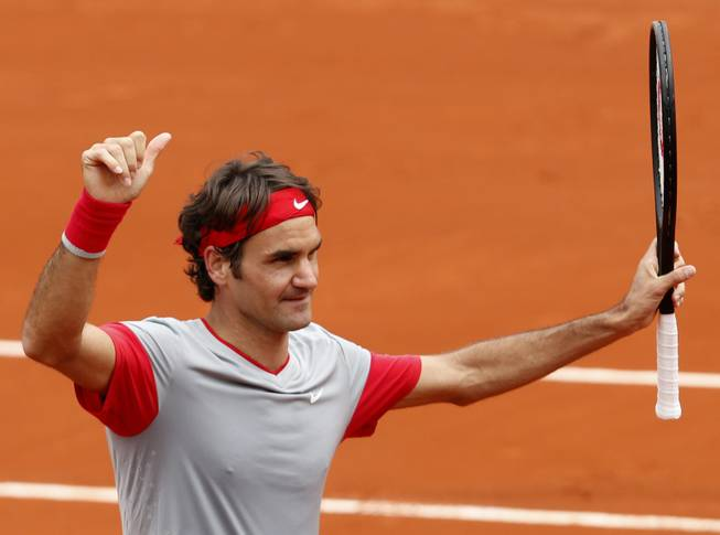 Switzerland's Roger Federer thumbs up after defeating Slovakia's Lukas Lacko in the first round match of the French Open tennis tournament at the Roland Garros stadium, in Paris, France, Sunday, May 25, 2014. Federer won 6-2, 6-4, 6-2.