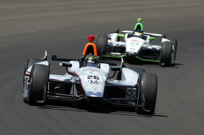 Kurt Busch (26) leads Sebastien Bourdais, of France, through the first turn during the 98th running of the Indianapolis 500 IndyCar auto race at the Indianapolis Motor Speedway in Indianapolis on Sunday, May 25, 2014.