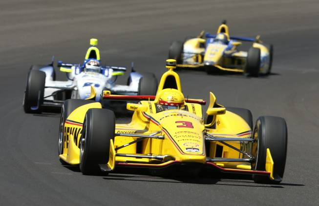 Helio Castroneves, of Brazil, leads JR Hildebrand, center, and Marco Andretti through the first turn during the Indianapolis 500 IndyCar auto race at the Indianapolis Motor Speedway in Indianapolis on Sunday, May 25, 2014.