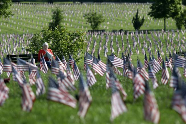 John Walaszek, of Old Bridge, N.J., is surrounded by flags for Memorial Day, as he relaxes on a bench at Brig. Gen. William C. Doyle Veterans Memorial Cemetery in Wrightstown, N.J., Sunday, May 25, 2014.