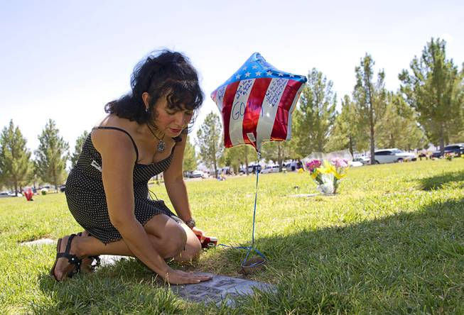 Victoria D. Garcia touches the grave marker for her father following a Memorial Day ceremony at the Southern Nevada Veterans Memorial Cemetery in Boulder City Monday, May 26, 2014.