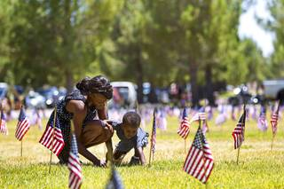 Teresa Brown and her son Keon, 2, visit the gravesite of Teresa's father Robert Brown, a Korean war veteran, before a Memorial Day ceremony at the Southern Nevada Veterans Memorial Cemetery in Boulder City Monday, May 26, 2014.