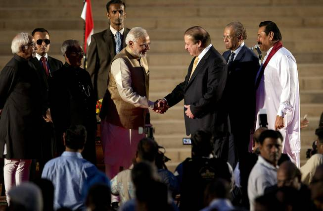 India's new prime minister Narendra Modi, center left, shakes hands with his Pakistani counterpart Nawaz Sharif, as Sri Lankan President Mahinda Rajapaksa, right, and Mauritius Prime Minister Navinchandra Ramgoolam, second right watch during Modi's inauguration in New Delhi, India, Monday, May 26, 2014. Modi took the oath of office as India's new prime minister at the sprawling presidential palace on Monday, a moment made more historic by the presence of the leader of archrival Pakistan. Indian President Pranab Mukherjee, third left and Indian Vice President Hamid Ansari, left, are also seen.