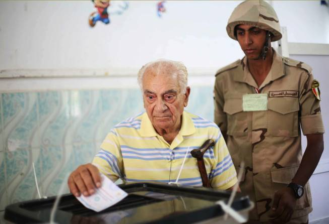 An Egyptian soldier watches a voter cast his ballot in the presidential election in Cairo, Egypt, on Monday, May 26, 2014. This week's key vote is taking place against a backdrop of the turmoil that has roiled the country since the 2011 ouster of Hosni Mubarak and the government's crackdown against Morsi's Muslim brotherhood and its allies since last July.