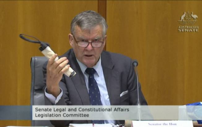 In this image made from ABC video, Sen. Bill Heffernan shows a fake pipe bomb during a committee hearing in Canberra, Australia, on Sunday, May 25, 2014. Heffernan, who represents the ruling Liberal Party, was making a point about a relaxation of security at Parliament House.