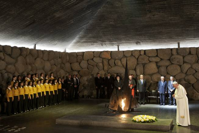Pope Francis lays a wreath as Israel's President Shimon Peres and Israeli Prime Minister Benjamin Netanyahu stand at the Hall of Remembrance at the Yad Vashem Holocaust memorial in Jerusalem on Monday, May 26, 2014. Francis honored Jews killed in the Holocaust and in terrorist attacks, and kissed the hands of Holocaust survivors as he capped his three-day Mideast trip with poignant stops Monday at some of the holiest and most haunting sites for Jews.