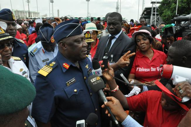 "Nigeria's chief of defense staff Air Marshal Alex Badeh, centre, speaks during a demonstration calling on the government to rescue the kidnapped girls of the government secondary school in Chibok, in Abuja, Nigeria, Monday, May 26, 2014. Scores of protesters chanting ""Bring Back Our Girls"" marched in the Nigerian capital Monday to protest the abductions of more than 300 schoolgirls by Boko Haram, the government's failure to rescue them and the killings of scores of teachers by Islamic extremists in recent years."