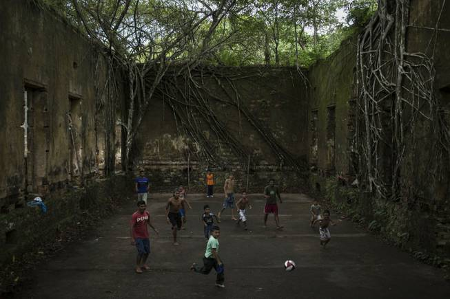 In this May 21, 2014, photo, children and adults play soccer in the ruins of Paricatuba, near Manaus, Brazil. Manaus is one of the host cities for the 2014 World Cup in Brazil.