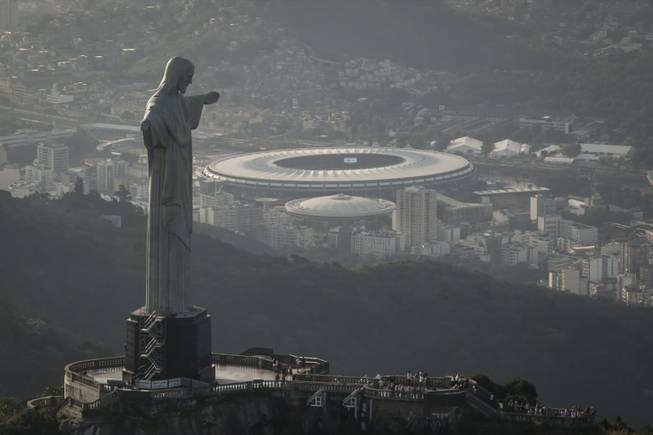 In this May 13, 2014, photo, this aerial view shot through an airplane window shows the Maracana stadium behind the Christ the Redeemer statue in Rio de Janeiro, Brazil. As opening day for the World Cup approaches, people continue to stage protests, some about the billions of dollars spent on the World Cup at a time of social hardship, but soccer is still a unifying force. The international soccer tournament will be the first in the South American nation since 1950.