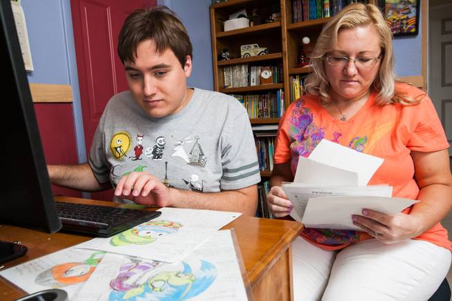 "Author Ben Nelson, 20, who is autistic and has recently published his first book ""Little Red Flying Hood,"" studies his artwork of characters in his new upcoming comic book alongside his mom, Laura, while working at his home in Henderson May 23, 2014."