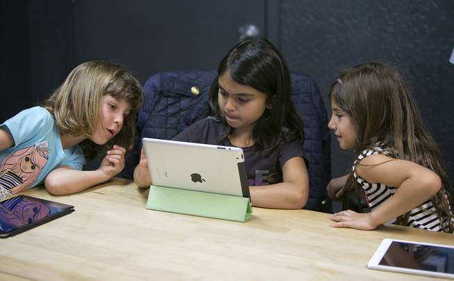 Anna Heath, 5, from left, Aryka Gunsagar, 6, and Rayah Ghosheh, 6, test Kidaptive's Leo's Pad app at the Kidaptive office in Palo Alto, Calif., May 7, 2014.