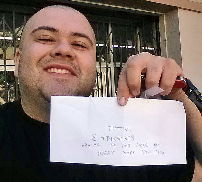 This image provided by Sergio Loza shows Loza holding up an envelope that had cash hidden in it in San Francisco on Sunday, May 25, 2014. Loza followed the clues from a Twitter user using the handle @HiddenCash to find the money.