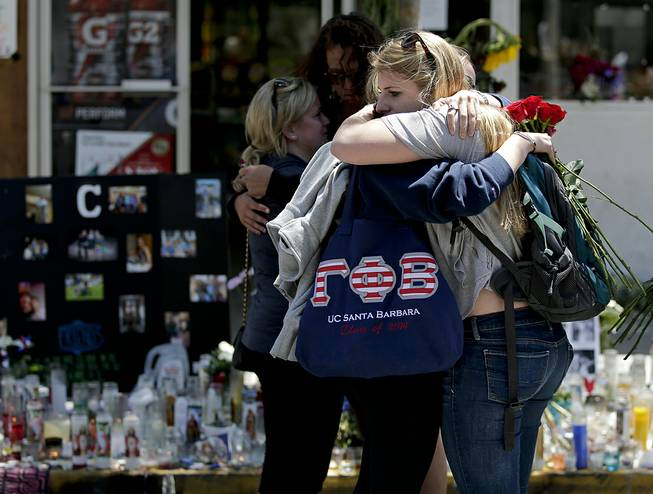 Mourners hug in front of the IV Deli Mart, where part of Friday night's mass shooting took place, on Tuesday, May 27, 2014 in the Isla Vista area near Goleta, Calif. Sheriff's officials said Elliot Rodger, 22, went on a rampage near the University of California, Santa Barbara, stabbing three people to death at his apartment before shooting and killing three more in a crime spree through a nearby neighborhood.