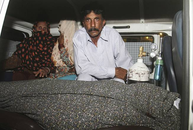 Mohammad Iqbal, right, husband of Farzana Parveen, 25, sits in an ambulance next to the body of his pregnant wife who was stoned to death by her own family, in Lahore, Pakistan, Tuesday, May 27, 2014.