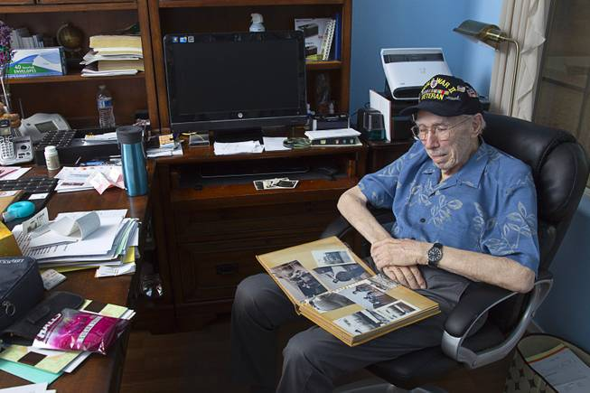 "World War II veteran Davis B. Leonard looks through a photo album at his home in Henderson Wednesday, May 28, 2014. Leonard and Gaetano ""Guy"" Benza, another local World War II veteran, will receive the French Legion d'Honneur award on Friday. The award is the highest honor France bestows on its citizens and foreign nationals."