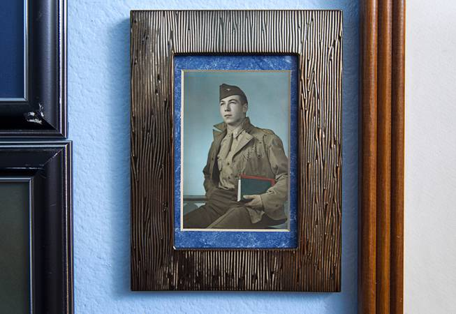 "A 1943 photo showing a 19-year-old Davis B. Leonard hangs in Leonard's home in Henderson Wednesday, May 28, 2014. Leonard and Gaetano ""Guy"" Benza, another local World War II veteran, will receive the French Legion d'Honneur award on Friday. The award is the highest honor France bestows on its citizens and foreign nationals."