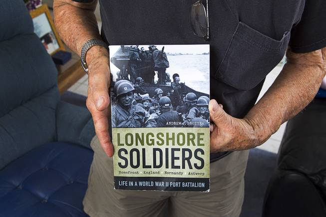 "World War II veteran Gaetano ""Guy"" Benza holds a book written about Longshore Soldiers at his home in North Las Vegas Wednesday, May 28, 2014. Benza served as a Longshoreman, Port Battalion 297th Port Company and saw action in the invasion of Normandy. Benza and Davis Leonard, another local World War II veteran, will receive the French Legion d'Honneur award on Friday. The award is the highest honor France bestows on its citizens and foreign nationals."