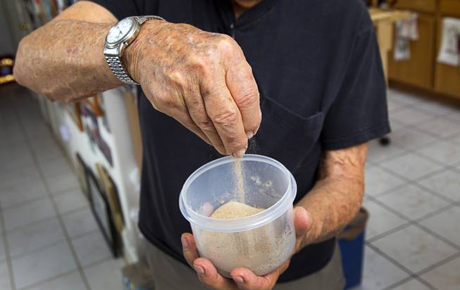 "World War II veteran Gaetano ""Guy"" Benza shows off sand,  collected during a 2009 visit to Omaha Beach, at his home in North Las Vegas Wednesday, May 28, 2014. Benza and Davis Leonard, another local World War II veteran, will receive the French Legion d'Honneur award on Friday. The award is the highest honor France bestows on its citizens and foreign nationals."