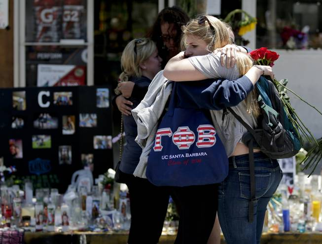 Mourners hug in front of the IV Deli Mart, where part of Friday night's mass shooting took place, on Tuesday, May 27, 2014 in the Isla Vista area near Goleta, Calif.